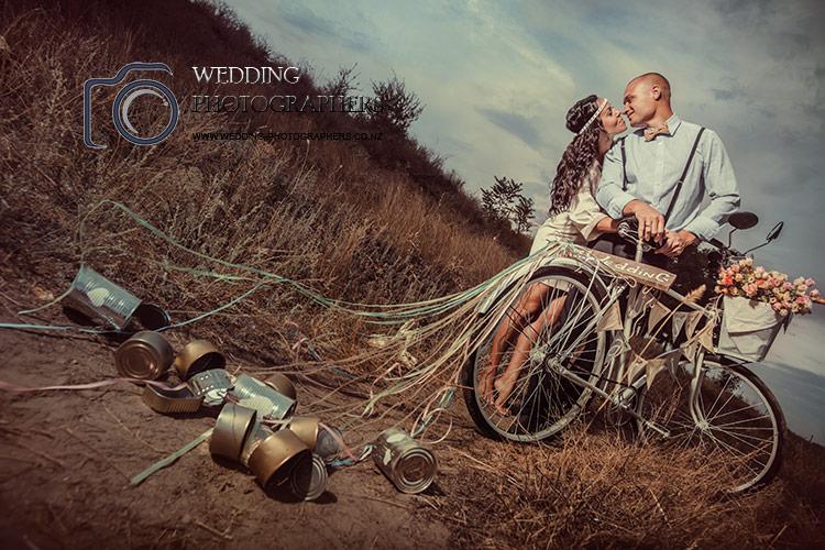 Just married wedding couple riding bike, Otago wedding photographers.